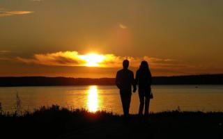 Пара влюбленных на закате у реки