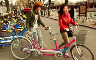 Девушки с двухместным велосипедом
